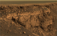 A view from Mars Exploration Rover Opportunity shows layered deposits in the wall of an impact crater. Studying layered deposits like these can help reveal the ancient history and climate of Mars.