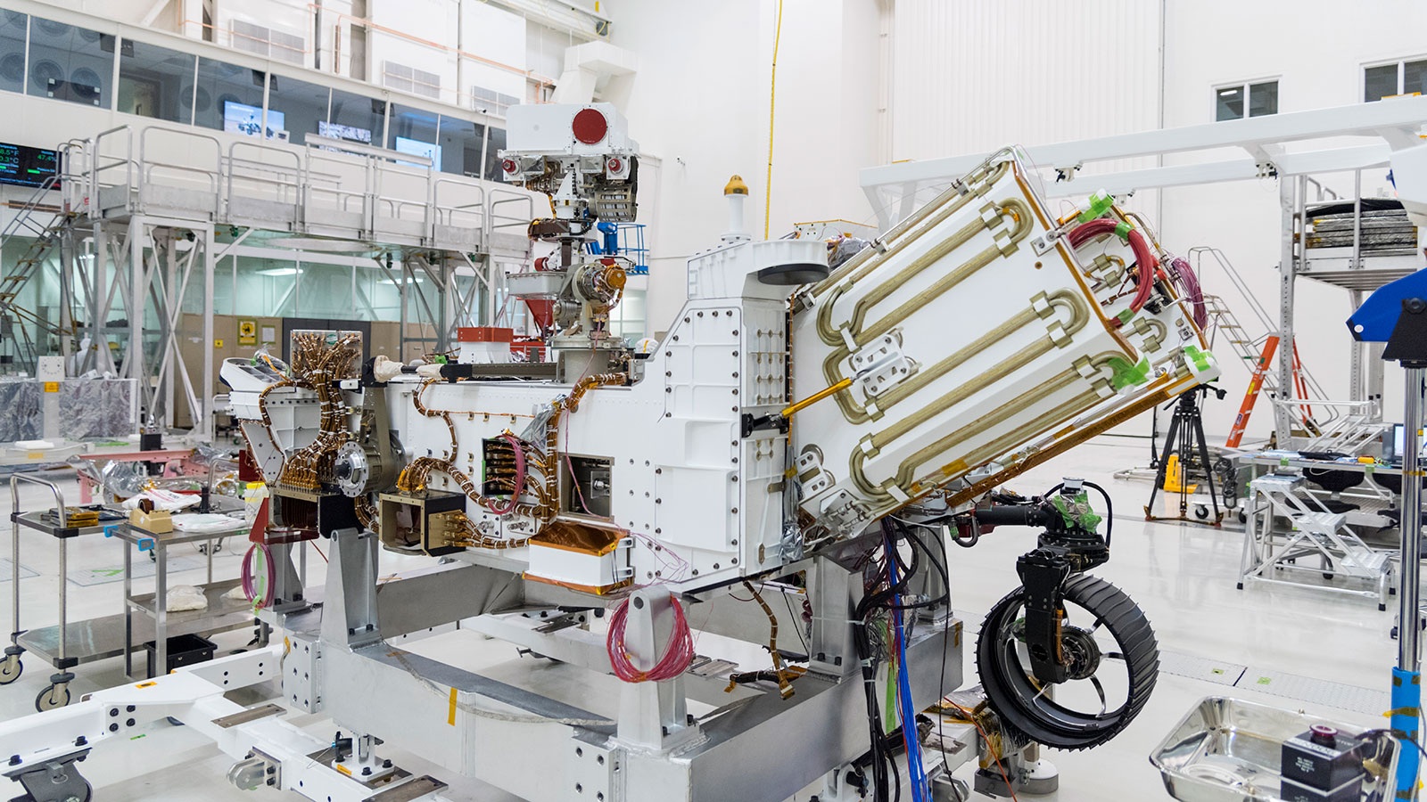 slide 5 - An image of the Mars 2020 rover in the JPL's Spacecraft Assembly Facility's High Bay 1