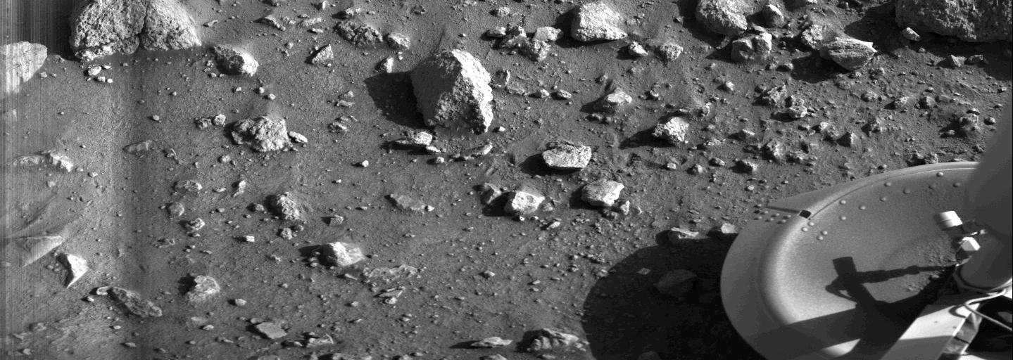 Black and white image shows Viking 1 footpad and rocks on the surface of Mars.